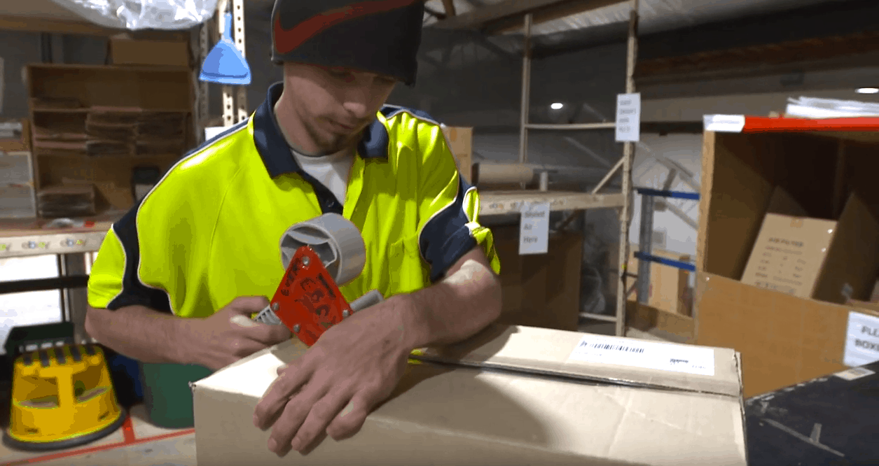 young man at work packing box high vis shirt