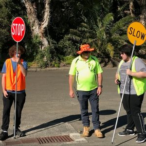 two participants and a trainer hold traffic control signs