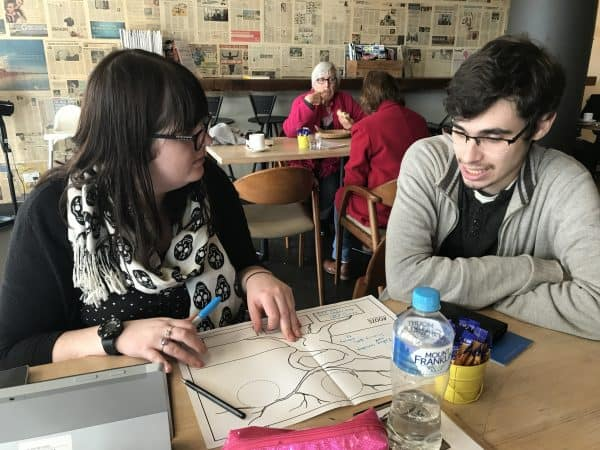 coach and young person working in cafe sticking together project