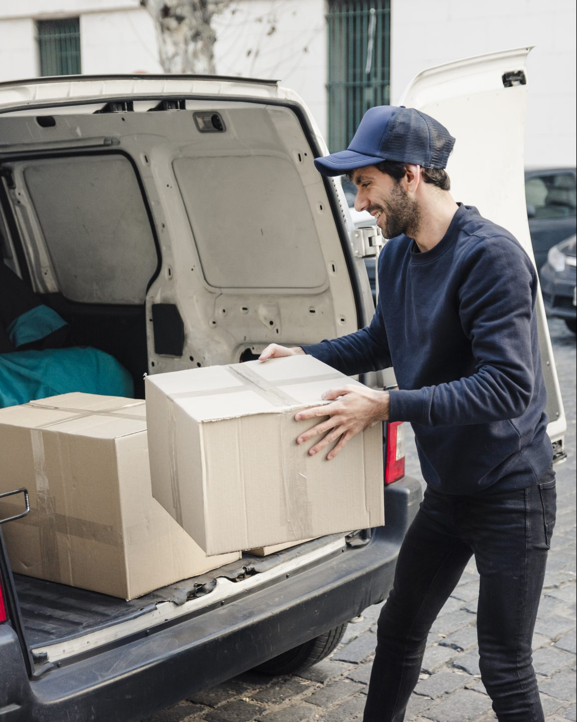 young man moving boxes into van