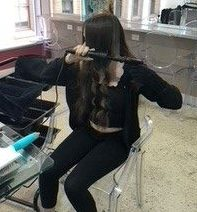 young girl curls hair in salon