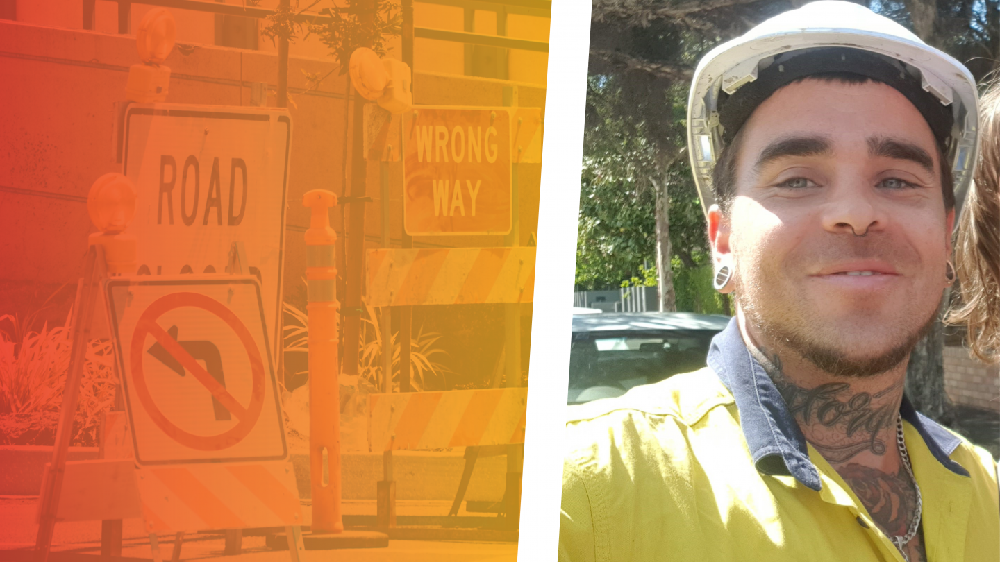 Joel in his work uniform, high vis vest hard hat. Background shows traffic signs.