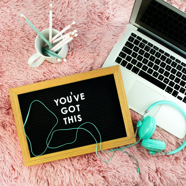 """""""You've Got This"""" lettering on pin sign next to laptop and headphones"""