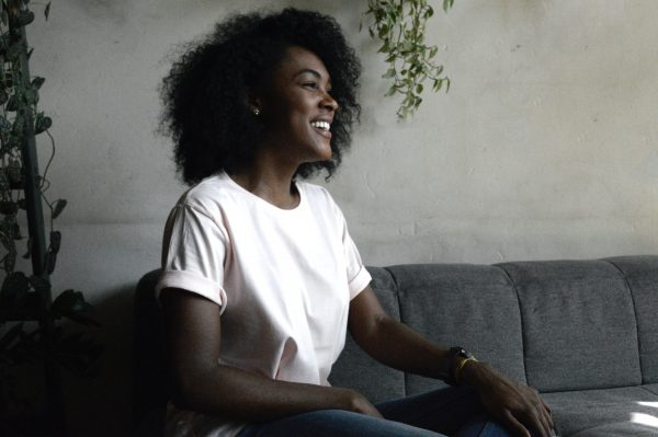 young black woman on couch - unsplash