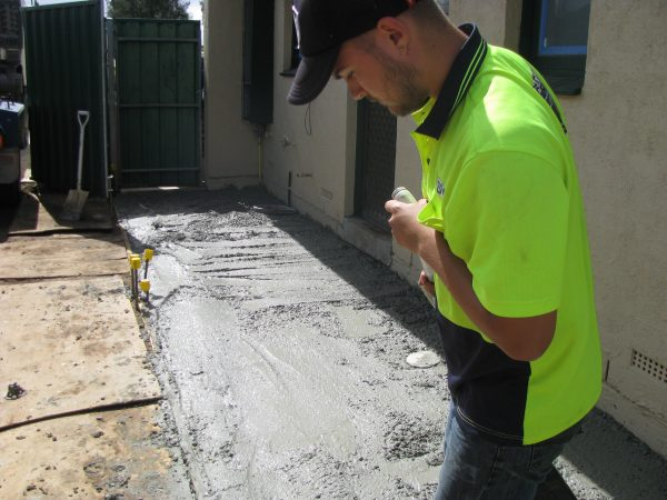young man doing concreting in high visibility top