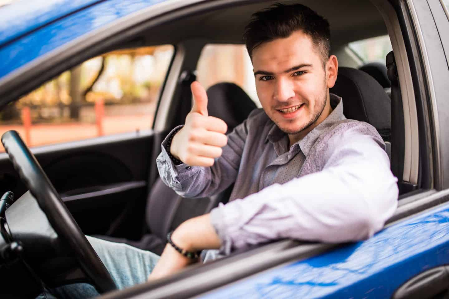 Happy smiling man sitting inside car showing thumbs up. Handsome