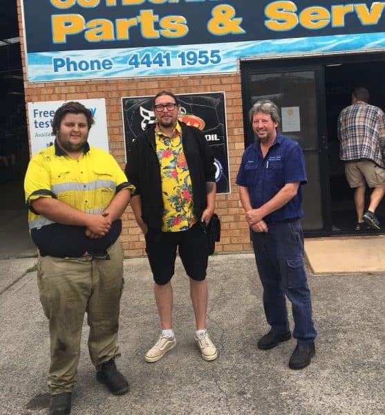 Jayden pictured with his Sticking Together Program Coach and his employer standing in front of his work,