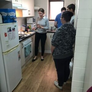 A group of young people in a kitchen learning new cooking skills with Lana.